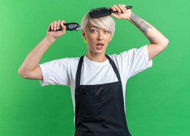 Überraschte junge schöne friseurin in uniform mit haarschneidemaschine mit kamm um den kopf isoliert auf grünem hintergrund