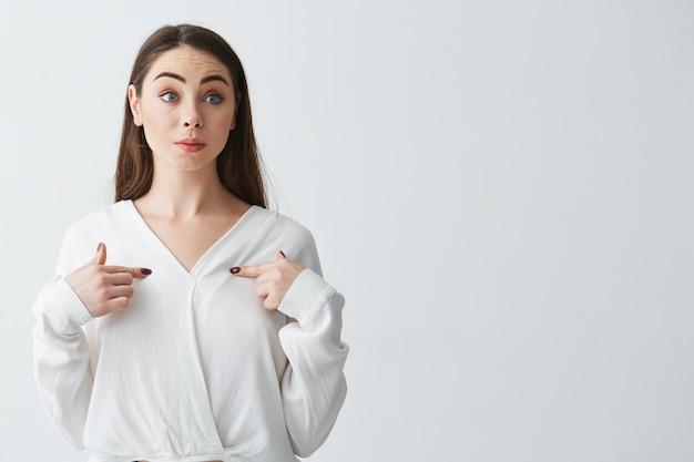 Überraschte junge schöne geschäftsfrau, die finger auf sich selbst zeigt.