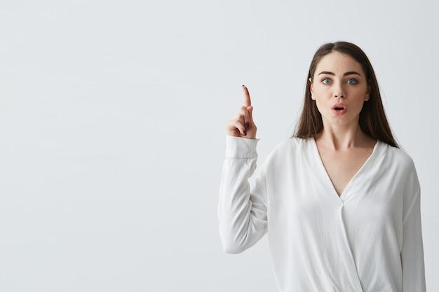 Überraschte junge schöne geschäftsfrau mit geöffnetem mund, der finger nach oben zeigt.