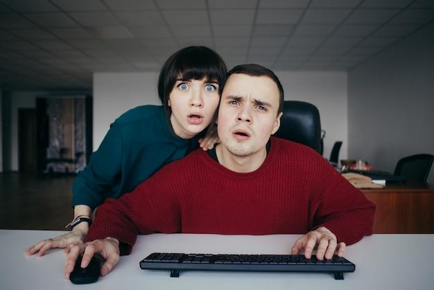 Überraschte junge schöne leute emotional büroangestellte, die einen computerbildschirm betrachten. die situation im büro