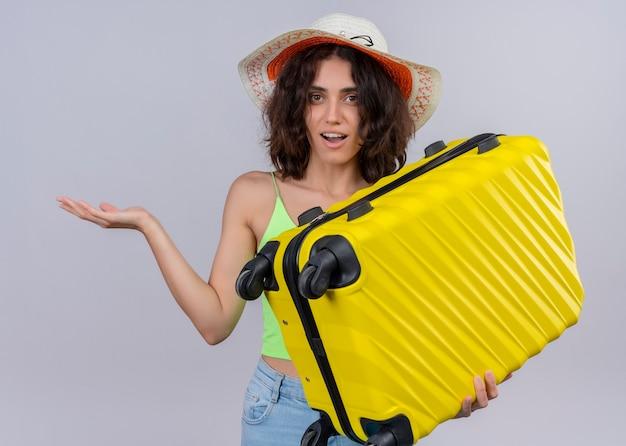 Überraschte junge schöne reisende frau, die hut trägt und koffer hält und leere hand auf isolierter weißer wand zeigt