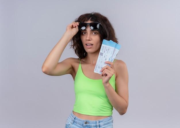 Überraschte junge schöne reisende frau, die sonnenbrille trägt und hält und flugtickets auf isolierter weißer wand hält