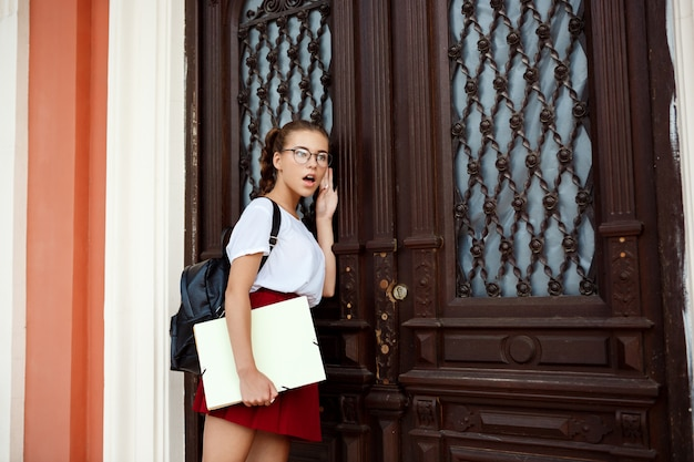 Überraschte junge schöne studentin in gläsern, die nahe tür stehen und lauschen.