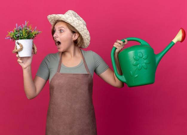 Überraschte junge slawische gärtnerin mit gartenhut, die gießkanne hält und blumen im blumentopf betrachtet
