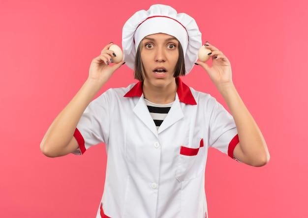 Überraschte junge weibliche köchin in der kochuniform, die eier lokalisiert auf rosa wand hält