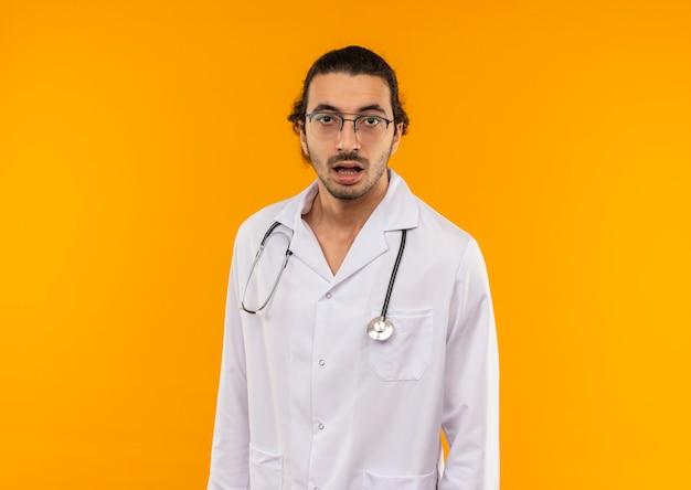 Überraschte jungen arzt mit medizinischer brille im medizinischen gewand mit stethoskop