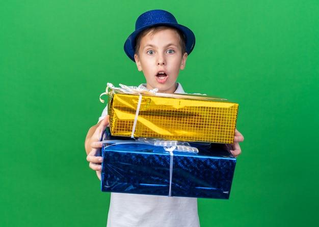 Überraschte jungen slawischen jungen mit blauem partyhut, der geschenkboxen lokalisiert auf grüner wand mit kopienraum hält