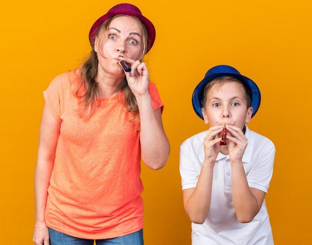 Überraschte jungen slawischen jungen mit blauem partyhut und seiner mutter, die violetten partyhut trägt, der partypfeifen bläst, die auf orange wand mit kopienraum isoliert werden