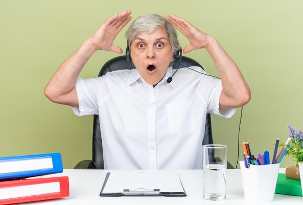 Überraschte kaukasische callcenter-betreiberin auf kopfhörern, die am schreibtisch mit bürowerkzeugen sitzen und die hände einzeln auf grüner wand heben