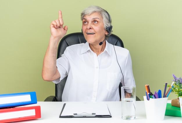 Überraschte kaukasische callcenter-betreiberin auf kopfhörern, die am schreibtisch sitzen und bürowerkzeuge suchen und nach oben zeigen, isoliert auf grüner wand