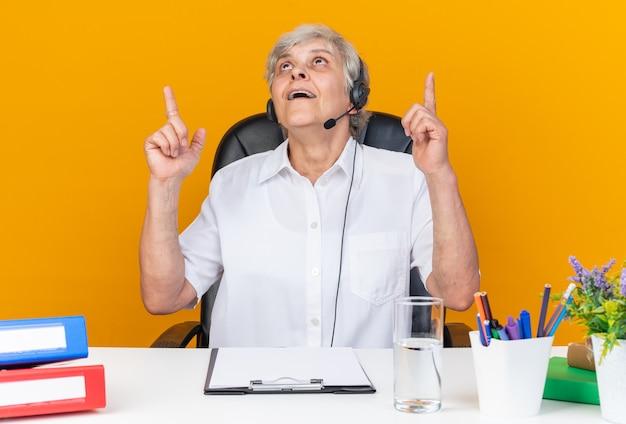 Überraschte kaukasische callcenter-betreiberin auf kopfhörern, die am schreibtisch sitzen und bürowerkzeuge suchen und nach oben zeigen
