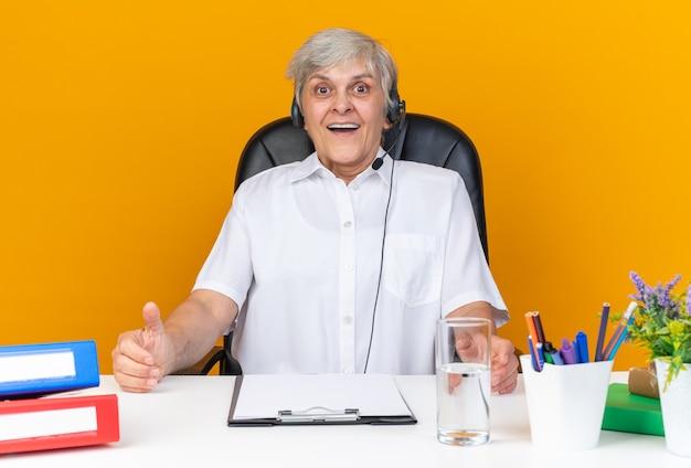 Überraschte kaukasische callcenter-betreiberin mit kopfhörern, die mit bürowerkzeugen am schreibtisch sitzen