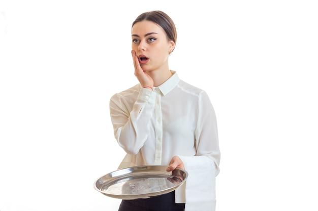 Überraschte kellnerin mit trey in händen und offenem mund isoliert auf weiß