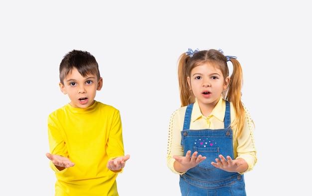 Überraschte kinder im vorschulalter schauen mit ausgestreckten armen in die kamera. weißer hintergrund und emotionskonzept.