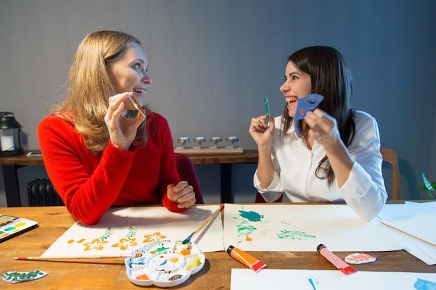 Überraschte kunstschüler, die mit schablonen arbeiten