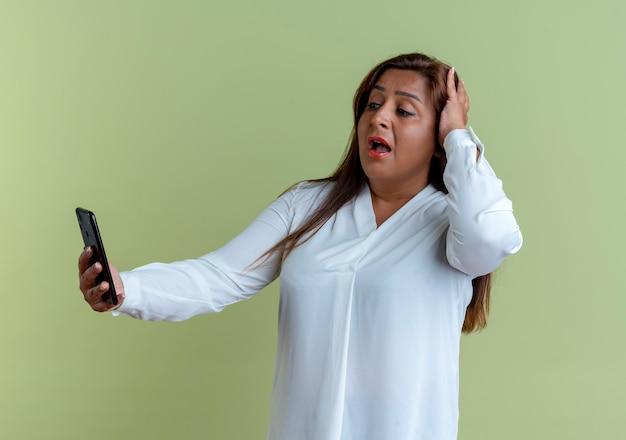 Überraschte lässige kaukasische frau mittleren alters, die telefon hält und betrachtet und kopf lokalisiert auf olivgrüner wand packte