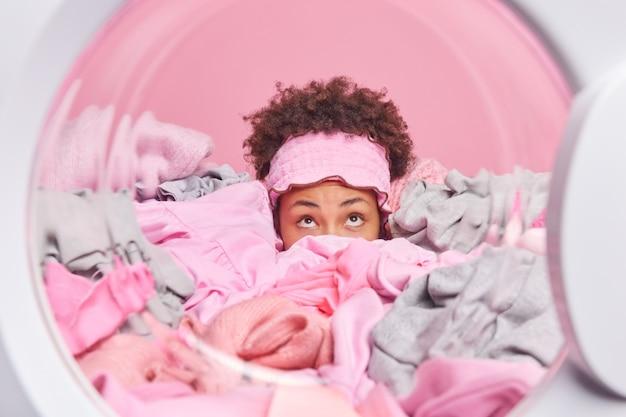 Überraschte, lockige frau, die mit einem großen wäschestapel bedeckt ist, der sich über posen in der waschmaschine konzentriert, die damit beschäftigt ist, schmutzige kleidung zu waschen, erledigt hausarbeiten