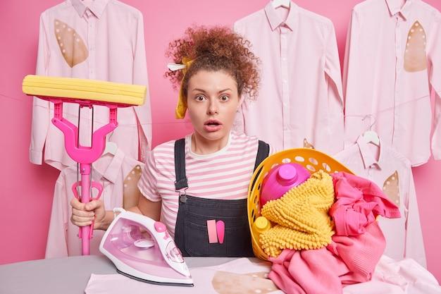 Überraschte lockige frau macht hausarbeit und hält mopp-posen in der nähe des bügelbretts mit wäschekorb schockiert, um so viel arbeit über das haus in freizeitkleidung zu tragen. housekeeping-konzept