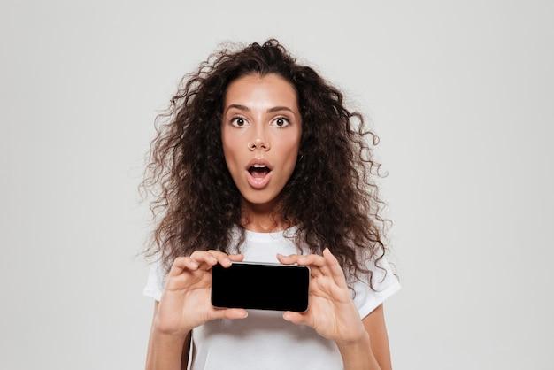 Überraschte lockige frau mit offenem mund, der leeren smartphonebildschirm zeigt