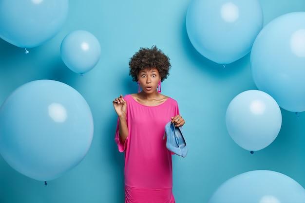 Überraschte lockige frau wählt outfit für perfekten geburtstag, trägt in rosa festlichem kleid und hält blaue schuhe mit hohen absätzen, merkt, dass sie vergessen hat, tasche zu kaufen. mode- und feierkonzept.