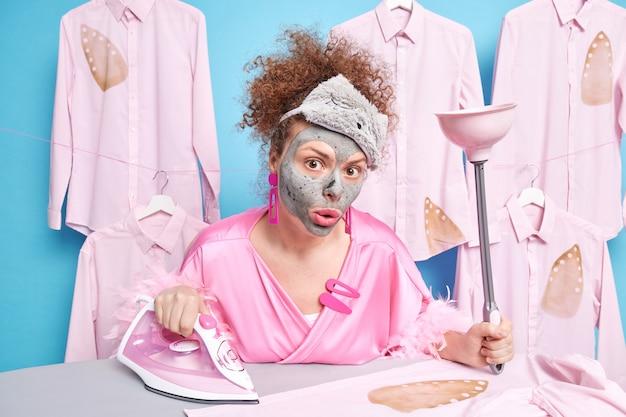 Überraschte lockige hausfrau unterzieht sich schönheitsbehandlungen während der hausarbeit trägt tonmaske auf das gesicht auf hält kolbenbügeleisen kleidung oder wäsche auf bügelbrett trägt schlafmaske und morgenmantel