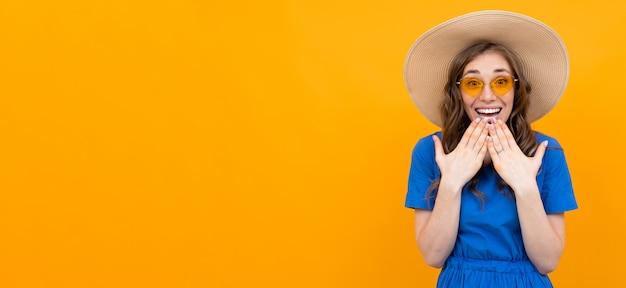 Überraschte mädchentouristin auf einer orange wand
