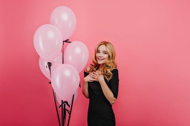 Überraschte modische dame, die während der feier aufwirft. erstauntes geburtstagskind, das nahe großen gruppe von partyballons steht.