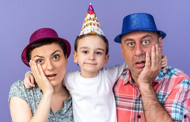 Überraschte mutter und vater mit partyhüten, die hände auf das gesicht legen, während ihr sohn isoliert auf lila wand mit kopienraum steht?