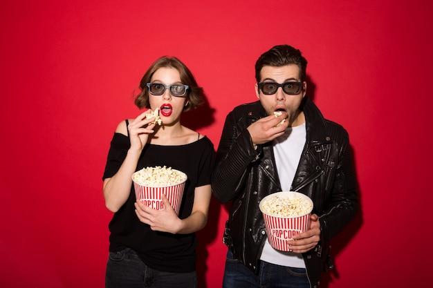 Überraschte punkpaare, die popcorn essen und schauen