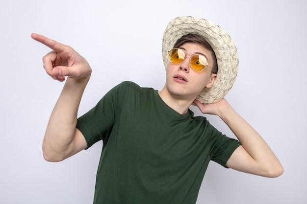 Überraschte punkte an der seite junger gutaussehender kerl mit hut mit brille isoliert auf weißer wand
