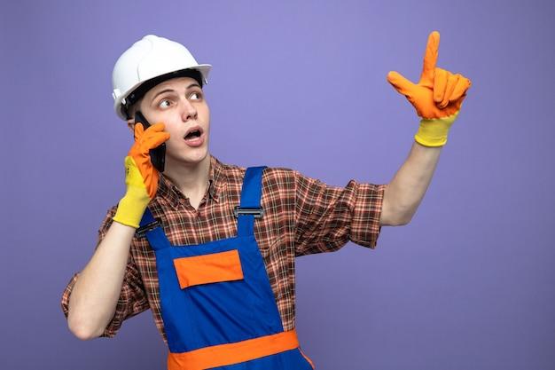 Überraschte punkte beim jungen männlichen baumeister, der uniform mit handschuhen trägt, spricht am telefon