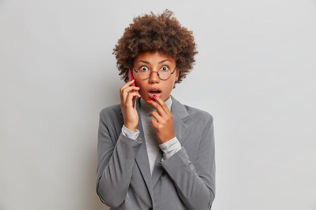 Überraschte regisseurin führt telefongespräche und starrt sprachlos in die kamera, um schockierende neuigkeiten zu erfahren