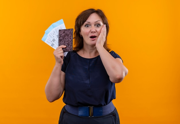 Überraschte reisefrau mittleren alters, die tickets und geldbörse hält und hand auf die wange legt