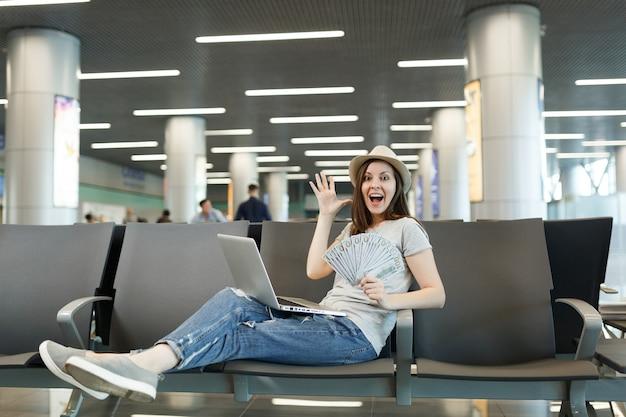 Überraschte reisende touristenfrau, die am laptop arbeitet, ein bündel dollar-bargeld hält, hände ausbreitend warten in der lobbyhalle am flughafen