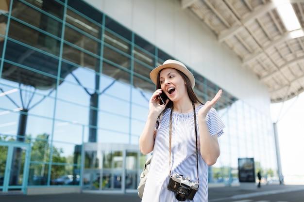 Überraschte reisende touristenfrau mit retro-vintage-fotokamera-gespräch auf handy, das freund anruft