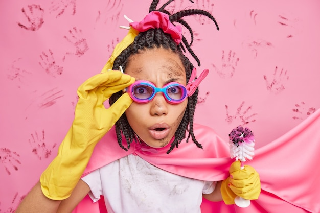 Überraschte schmutzige ethnische frau trägt eine schutzbrille, die wie ein superheld gekleidet ist, der eine toilettenbürste hält und schnell posen gegen die rosa wand reinigt