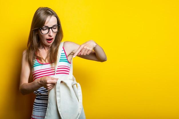 Überraschte schockierte junge frau, die in leinentasche schaut und mit finger auf gelbem hintergrund zeigt.