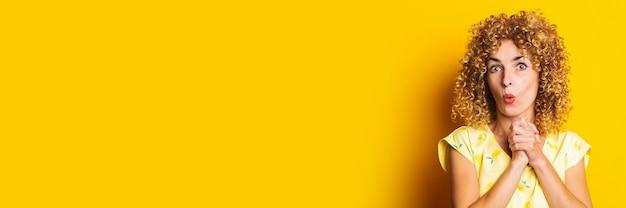 Überraschte schockierte junge frau mit lockigen haaren und faltigen handflächen unter dem kinn auf gelbem grund