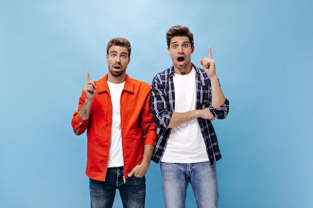 Überraschte schockierte jungs haben eine idee. mann in orangefarbener jacke und sein freund in kariertem hemd zeigen nach oben für text an der blauen wand.