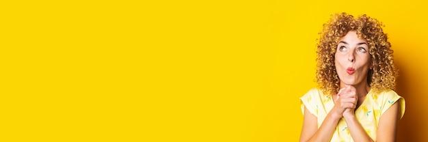 Überraschte schockierte lockige junge frau mit gefalteten händen unter dem kinn auf gelbem grund