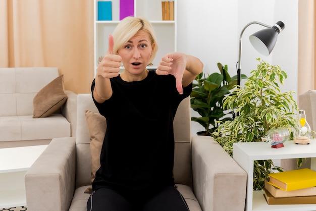 Überraschte schöne blonde russische frau sitzt auf sessel daumen hoch und daumen runter und schaut auf die kamera im wohnzimmer