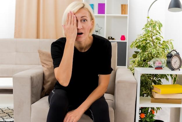 Überraschte schöne blonde russische frau sitzt auf sessel, der auge mit hand im wohnzimmer schließt