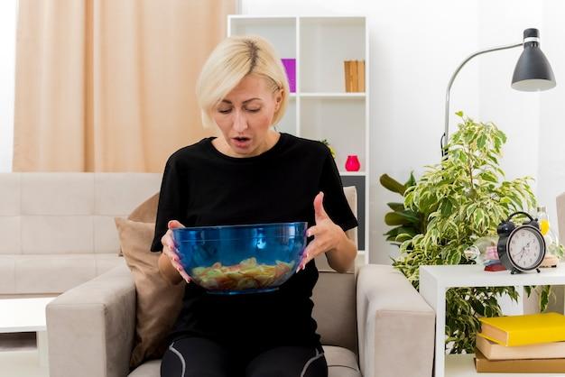 Überraschte schöne blonde russische frau sitzt auf sessel, der schüssel von chips hält und betrachtet