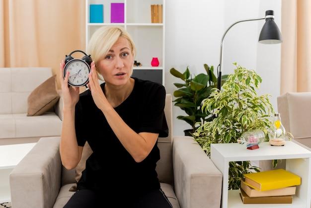 Überraschte schöne blonde russische frau sitzt auf sessel, der wecker hält, der schaut