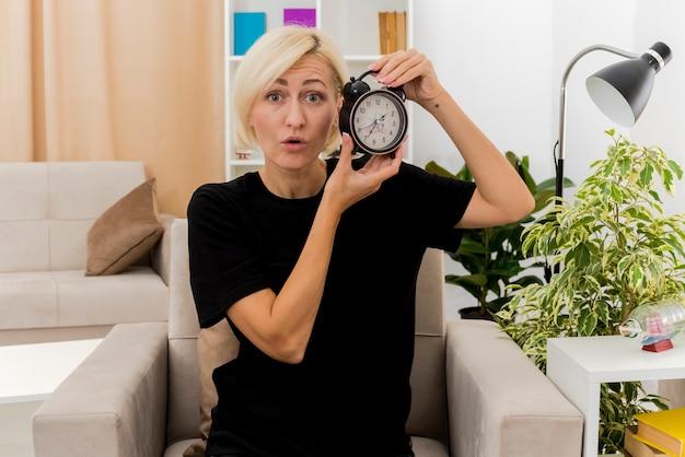 Überraschte schöne blonde russische frau sitzt auf sessel, der wecker im wohnzimmer hält