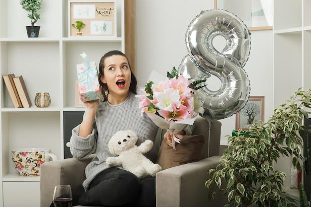 Überraschte schöne frau am glücklichen frauentag, der geschenk mit blumenstrauß hält, der auf einem sessel im wohnzimmer sitzt