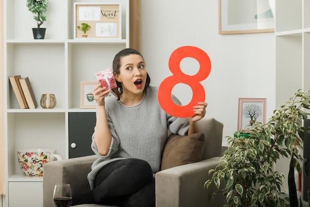 Überraschte schöne frau an einem glücklichen frauentag, der ein geschenk mit der nummer acht hält, die auf einem sessel im wohnzimmer sitzt