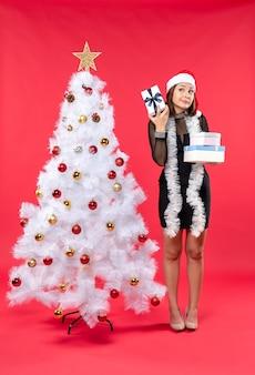 Überraschte schöne frau mit weihnachtsmannhut und stehend nahe dem geschmückten weihnachtsbaum, der geschenke auf rot hält