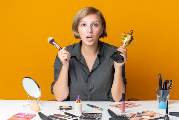 Überraschte schöne frau sitzt am tisch mit make-up-tools und hält siegerpokal mit make-up-pinsel