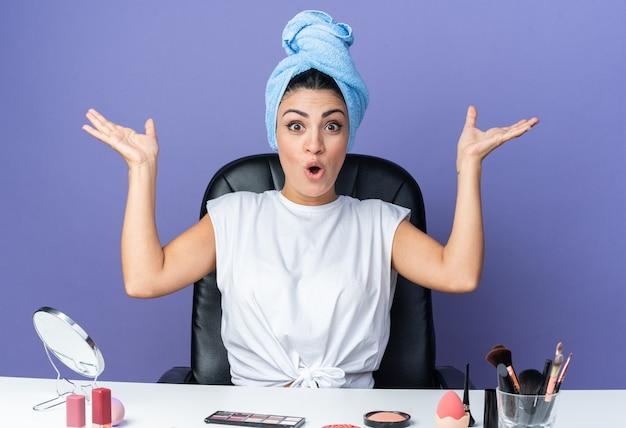 Überraschte schöne frau sitzt am tisch mit make-up-werkzeugen umwickelte haare in handtuch heben die hände